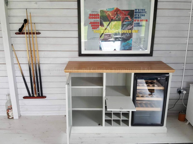 Made to measure sideboard with wine rack below drinks cupboard, wine chiller to side, cupboard with adjustable shelves on left side made with solid oak top, painted light grey