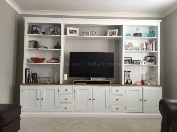 large wide tv storage solution with shelving and cupboards painted white