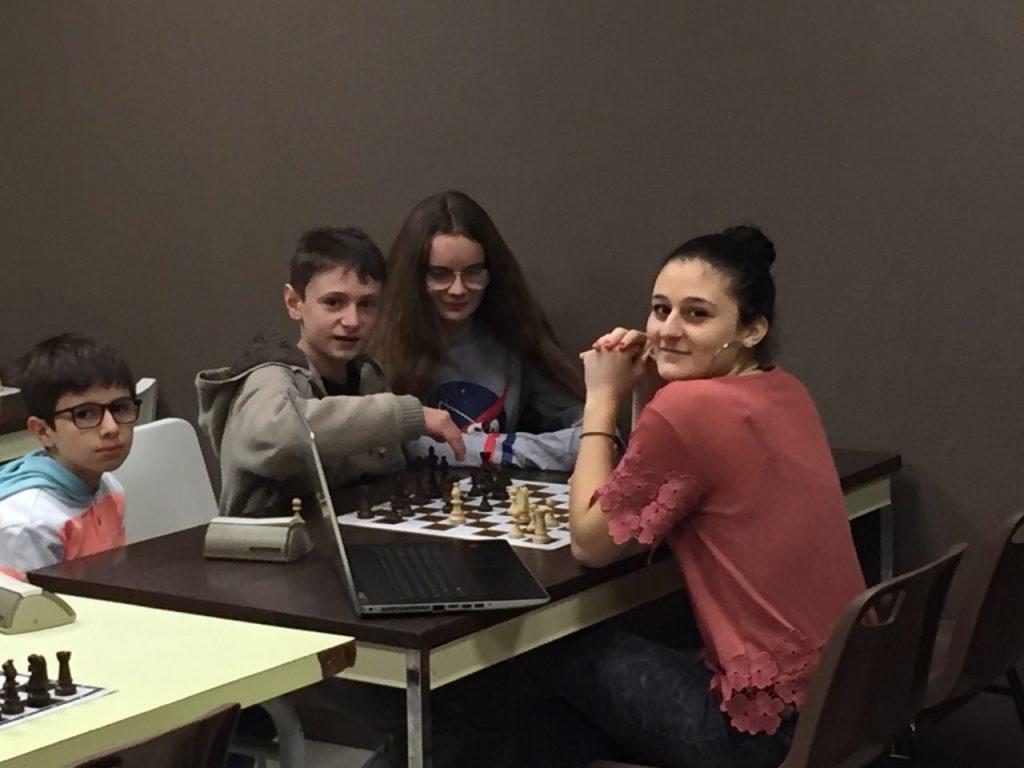 3 des jeunes champions Ali, Paulin et Lucie, avec leur professeur, Mariam.