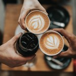 photo of people clinking coffee cups
