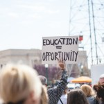 "Man holding a sign which reads ""education = opportunity""."