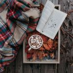 Leaves with a scarf, journal, and hot cocoa