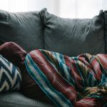 A person napping on the couch with a blanket over them