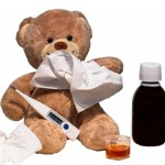 A teddy bear with a tissue, medicine, a thermometer, and other flu stuff