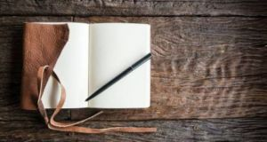 A notebook and pen on a wooden desk
