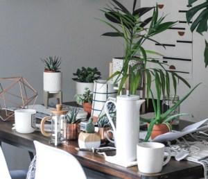 plante et tasse de thé posée sur une table en bois, entourée de chaise blanche