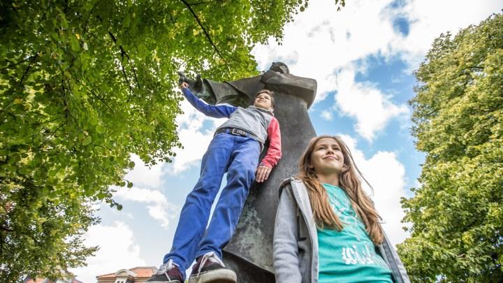 Zwei Kinder mit dem Denkmal von Nathan dem Weisen