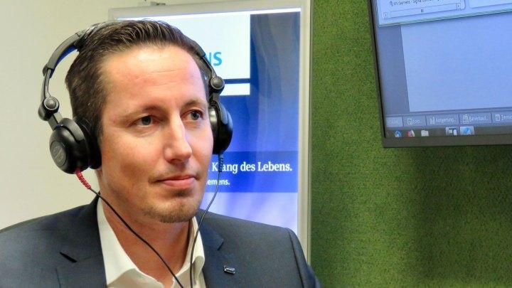 Martin Veit hat Kopfhörer auf den Ohren, als er mir demonstriert, wie ein Hörtest funktioniert.