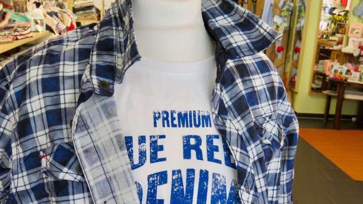 """Für """"coole"""" Jungs gibt es zum beispiel ein blau-weiß-kariertes Hemd über einem weißen T-Shirt mit blauer Schrift."""
