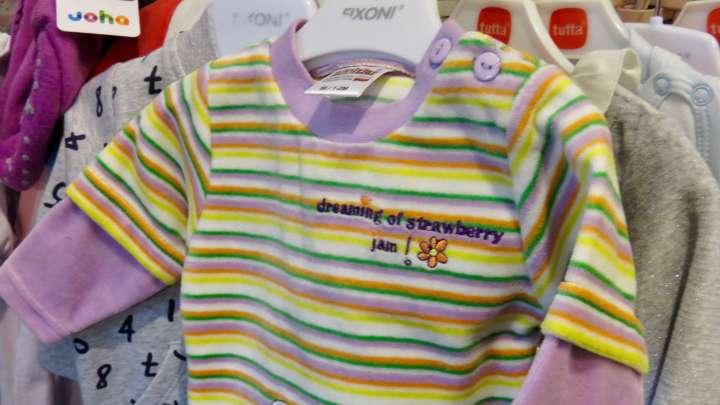 """Auf einem Babystrampler steht auf Englisch: """"Dreaming of strawberry jam!"""" (Die Übersetzung lautet: Ich träume von Erdbeermarmelade!"""")."""