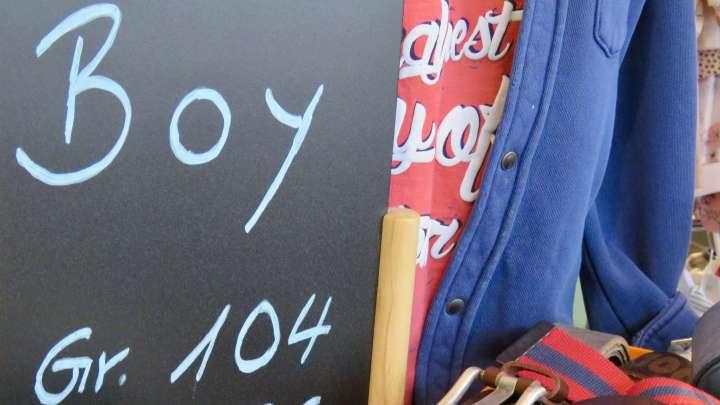 Auf einer Tafel steht auf Englisch des Wort Junge, um zu zeigen, dass es hier Kleidung für Jungs gibt.