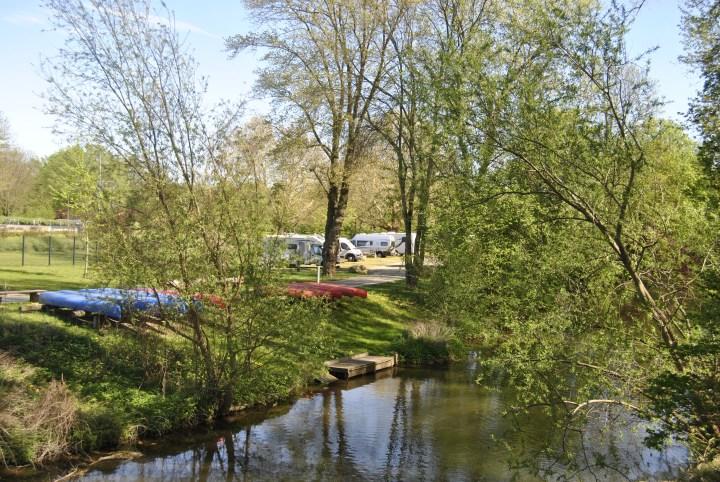 Fluss Oker mit Kanus an Land und Wohnmobilen im Hintergrund