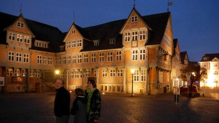 Das beleuchtete Wolfenbütteler Rathaus bei Nacht. Im Vordergrund ein drei Personen.