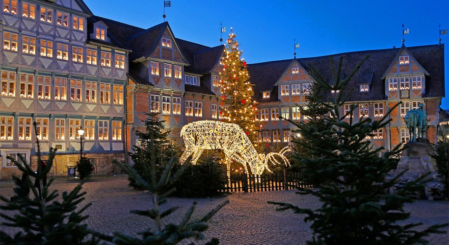Das festlich beleuchtete Fachwerk-Rathaus, im Vordergrund ein leuchtender Hirsch