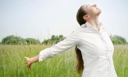 woman breathing air in field