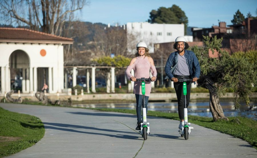 Zwei Nutzer fahren mit E-Scootern des Verleihers Lime auf einem an einem Brunnen liegenden Asphaltweg, Foto: Lime