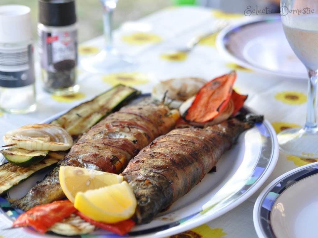 Serve the grilled fish with grilled vegetables and some lemon slices.