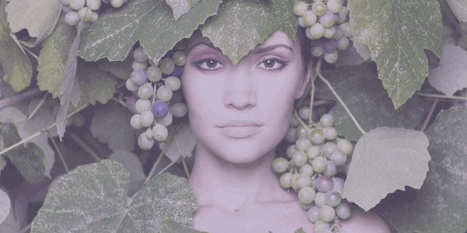 Mother Earth goddess figure surrounded by grapes and grape leaves