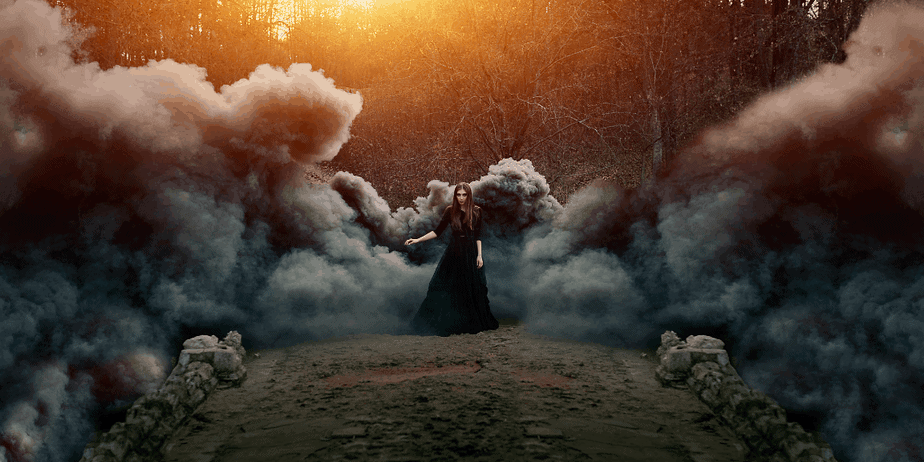 A witch standing in a foggy magical forest