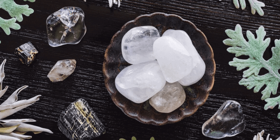 Assorted crystals and herbs laying on a wooden table