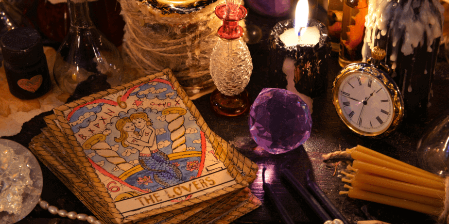 A table covered in witchcraft items like crystals, candles, and tarot cards