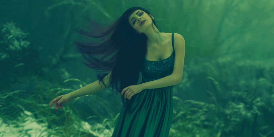 A green witch dancing in a snow-covered forest