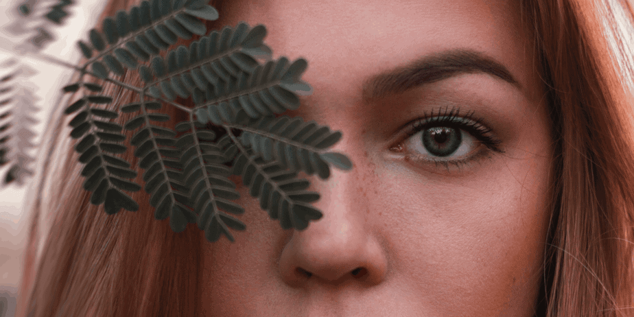 A woman holding a fern over her eye