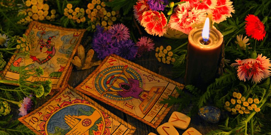 Tarot cards, a candle, flowers and a crystal on a table