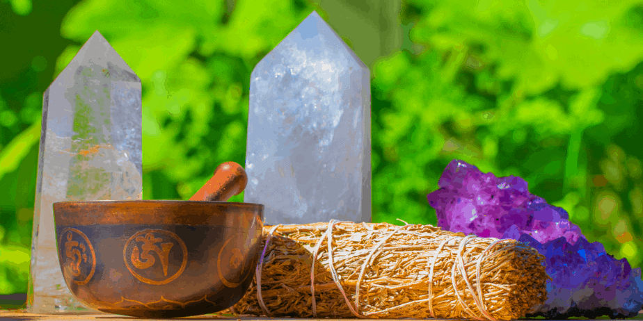 An herb bundle, singing bowl, and crystals sitting outside under the sun