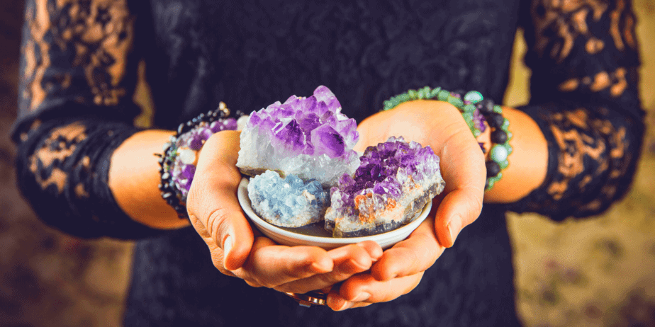 A woman holding a bowl of brightly colored healing crystals