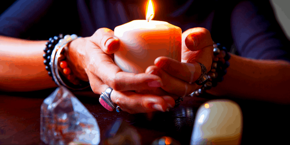 A woman holding a candle in front of two crystals