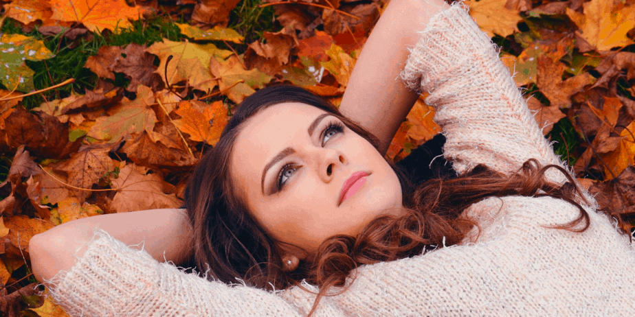 A woman laying on autumnal leaves and looking up to the sky while trying to decide what her pagan name will be
