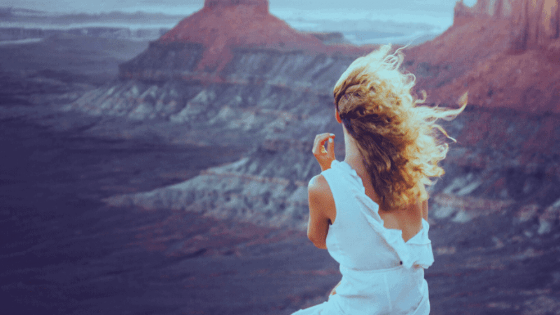Decorative image of a woman sitting in a canyon with a ripped dress, air flowing through her hair