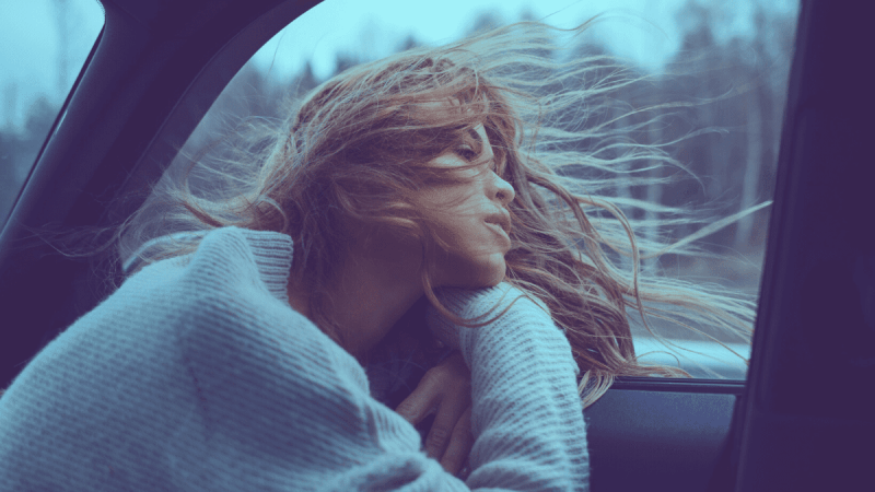 Decorative image of a woman with her head out of a car window with the air element blowing through it