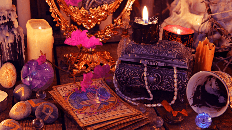 Decorative image of a witch's table, full of runes, tarot cards, and other trinkets of the occult