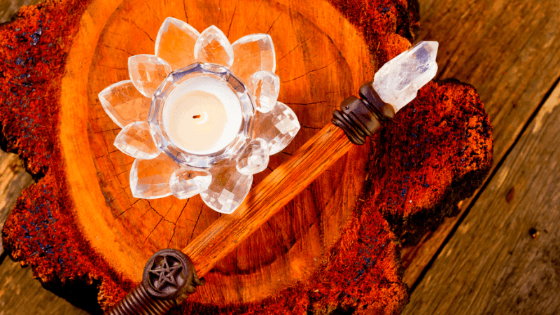 Decorative image of a wand with a crystal and a lotus candle holder on a wooden table