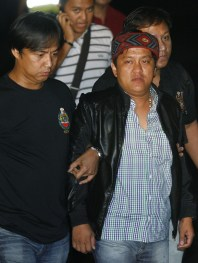 Agents of the National Bureau of Investigation escort Andal Ampatuan Jr. (R), a local mayor in Maguindanao province after he surrendered in Ampatuan in southern Philippines, upon his arrival at the Villamor air base in Pasay city, metro Manila, November 26, 2009. Philippine police filed murder charges on Thursday against the main suspect in the massacre of 57 people in the south of the country this week as authorities moved to dismantle his clan's control over the region. REUTERS/Romeo Ranoco (PHILIPPINES POLITICS CRIME LAW)