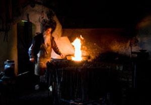 Smith using coal to heat metal