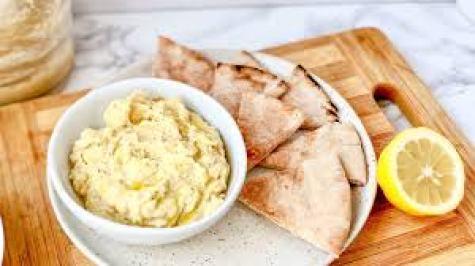Photo of a bowl of hummus, pita bread and a lemon half