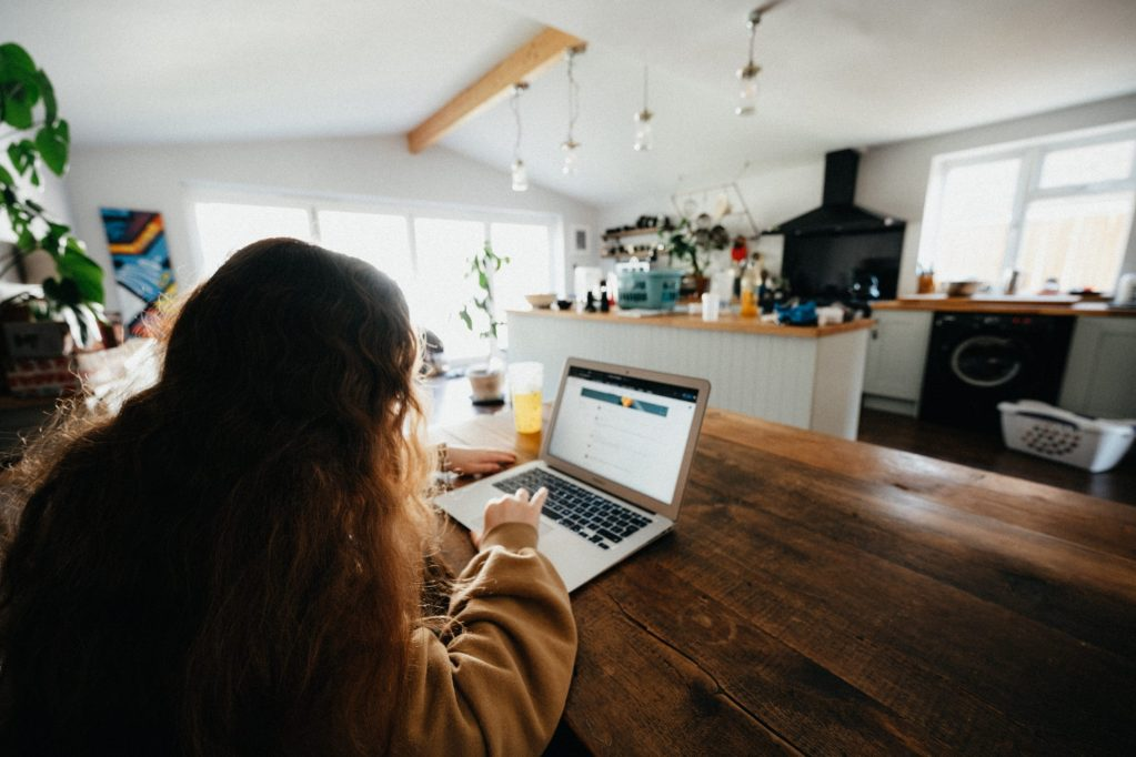Woman working on a laptop in a busy home, much like me during Lockdown