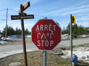 French, Cree syllabics, Cree, and English on traffic and street signs in the village.