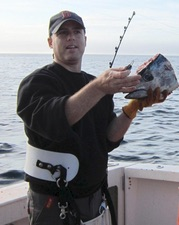 Researcher Gilad Heinisch holds a tuna head. He is sampling the brain cavity for hormones. Photo: Large Pelagics Research Center, UMass Amherst