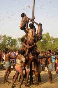 Santal-Männlichkeit. An einem mit Mobilöl beschmierten Pfahl versuchen mehrere Teams hinaufzuklettern, um die Trophäe zu holen.
