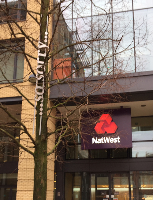 """words """"...so sorry"""" installed in a tree outside a branch of the Nat West"""