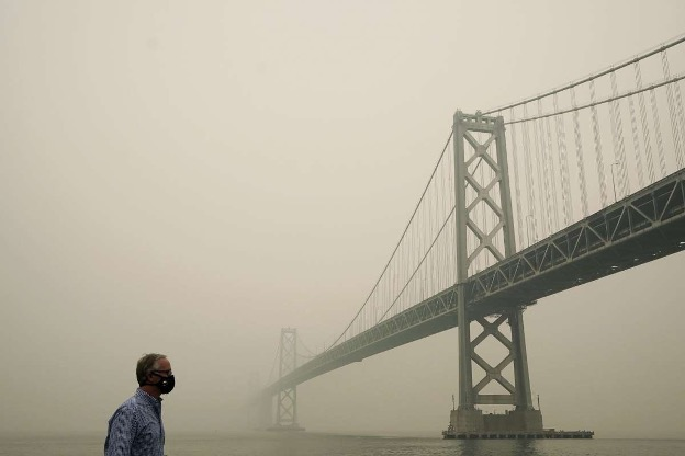 A person wearing a mask surrounded by wildfire smoke near Golden Gate Bridge