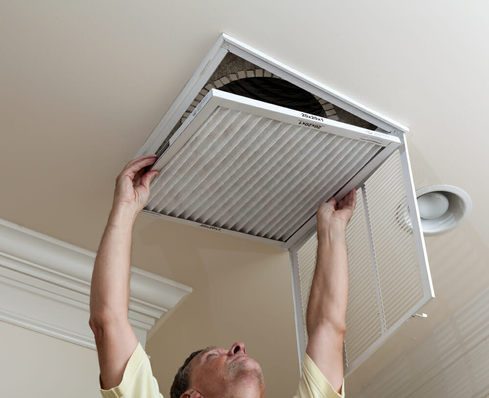 A person installing an HVAC filter into a vent on the ceiling