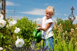 bigstock-Little-girl-watering-the-flowe-12193742