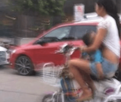 Crazy Breastfeeding:  Chinese woman breastfeeds on moped
