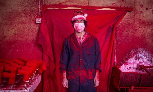 Photo by Imaginechina/REX (4301626b) 19-year-old worker Wei wearing a face mask and a Christmas hat covered in red powder Christmas decorations being made at a factory in Yiwu city, Zhejiang province, China - 15 Dec 2014