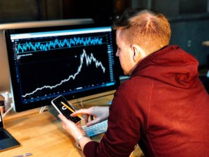 A young man checks his stock price chart on a computer screen